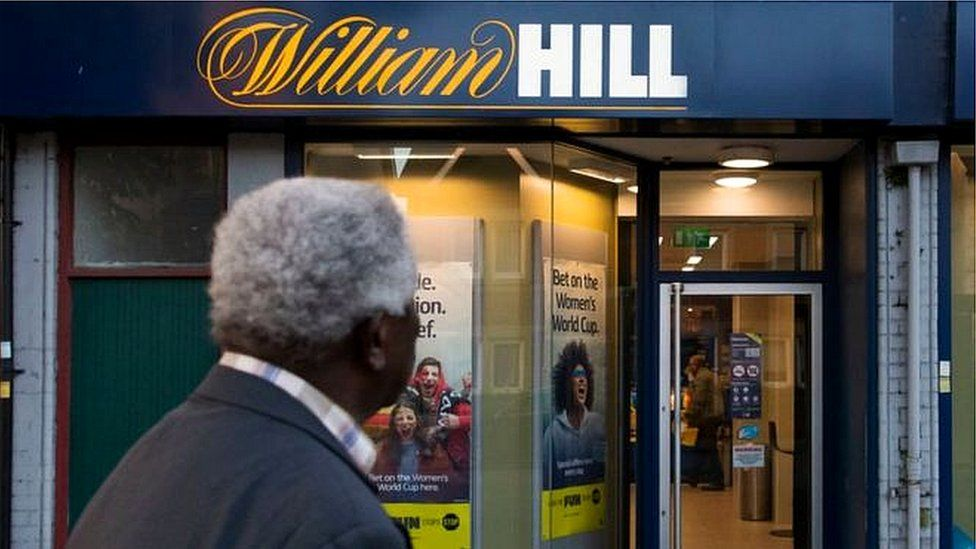 Man stands outside William Hill shop