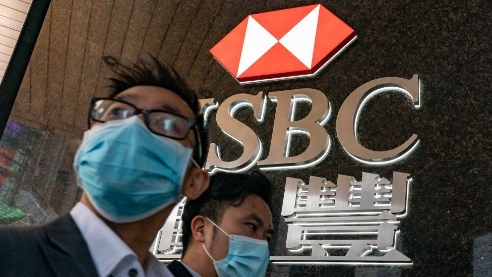 Pedestrians wearing face masks walk in front of a HSBC signage.