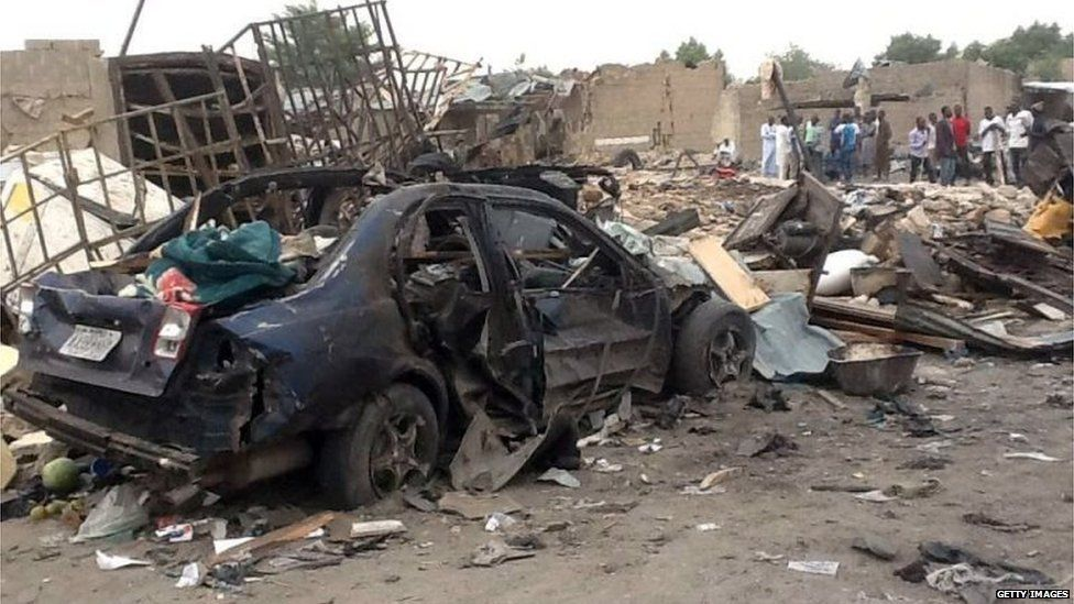 """People gather on March 2, 2014 near the wreckage at the scene where two explosions rocked a crowded neigbourhood in Maiduguri""""s Gomaris district on the evening of March 1"""