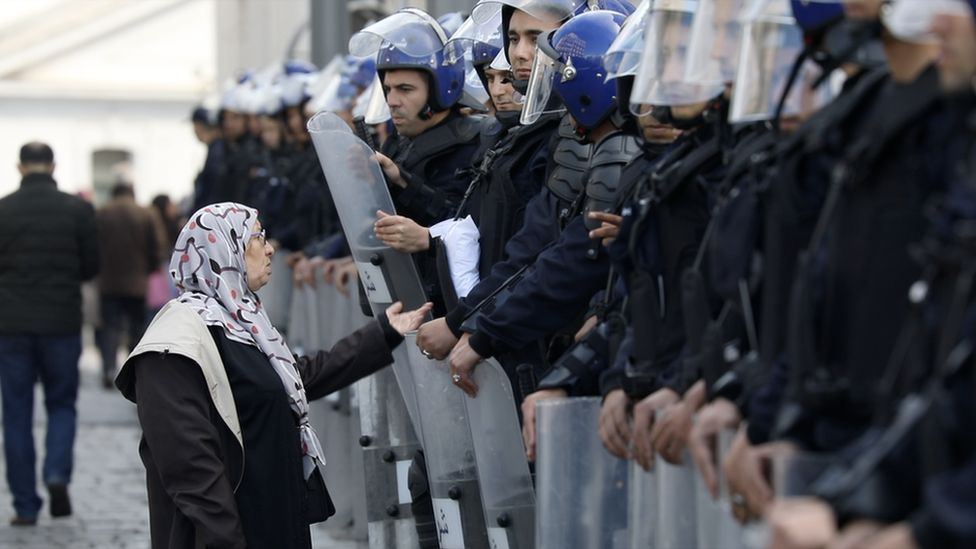 Nissa Imad confronting a line of riot police in Algeria