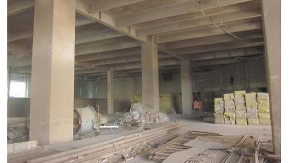 The inside of the building shows dusty floors and construction materials