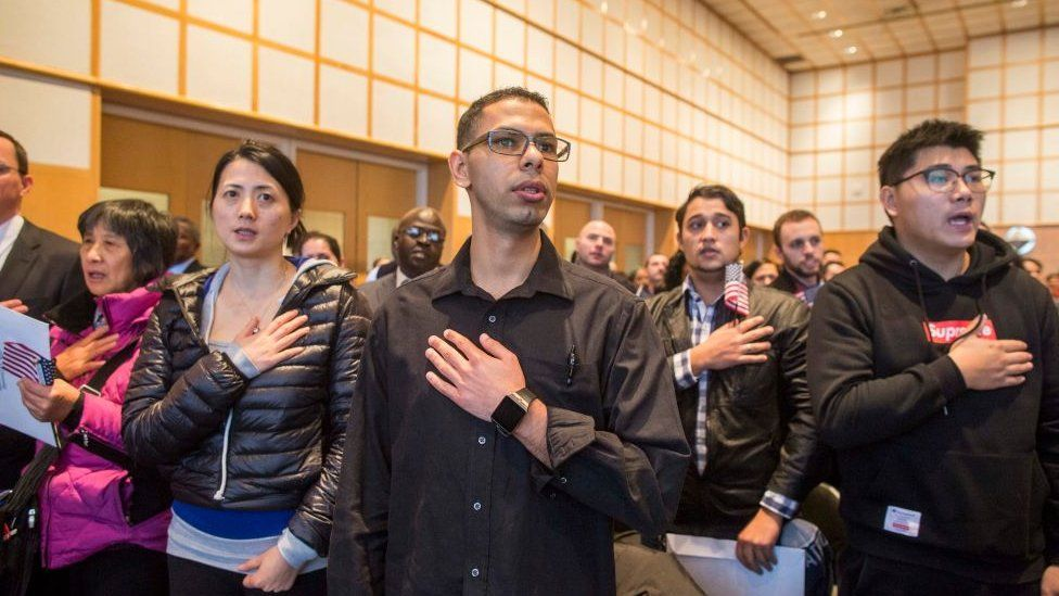 : A group of over 200 immigrants during the singing of the National Anthem at a Naturalization Oath Ceremony at the John F. Kennedy Presidential Library and Museum on February 8, 2017