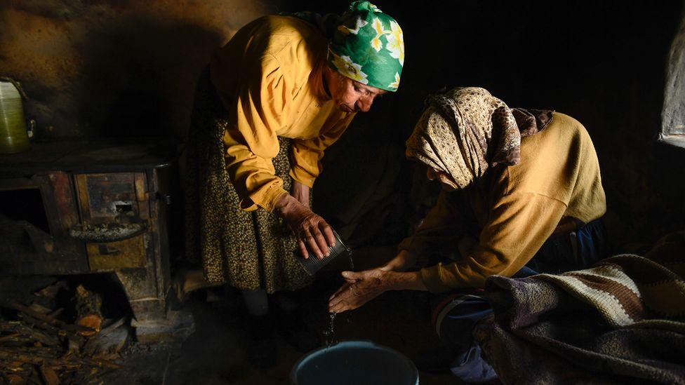 Hatidze is helping her mother Nazife to wash hands