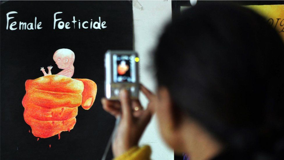 A young girl, Aman Kaur takes a photograph of paintings displayed during the opening of the art exhibition 'Female Foeticide' at Virsa Vihar hall in Amritsar on January 25, 2009
