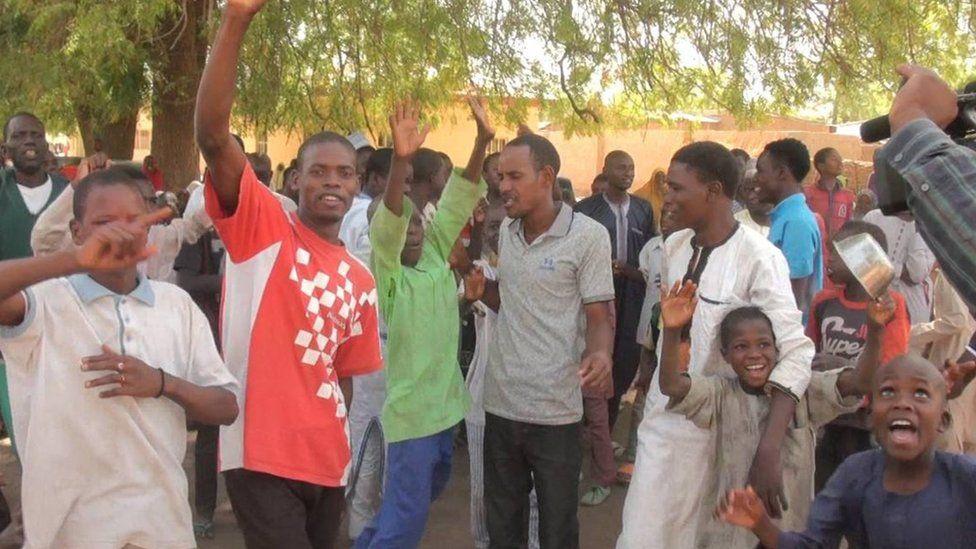People waving their arms in joy in Dapchi
