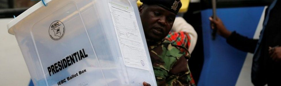 A security policeman unloads sealed ballot boxes from a bus to the Jamuhuri High School tallying center in Nairobi