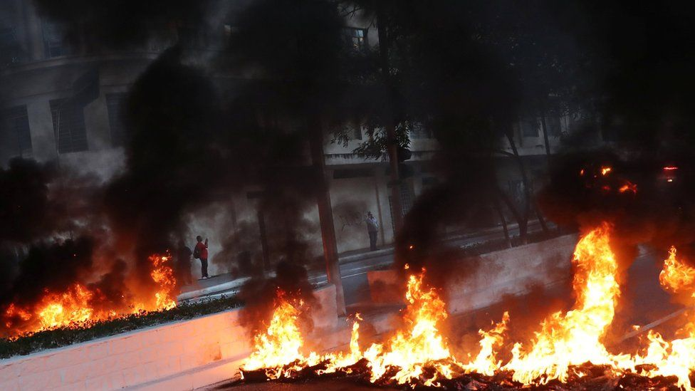 A man stands behind a row of burning tyres blocking the street during a general strike in Sao Paulo