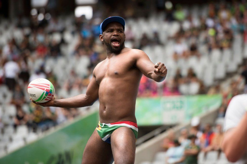 A South African rugby supporter wearing flag-print swimming trunks throws the ball.