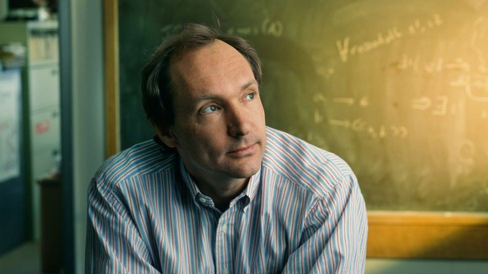 Sir Tim, looking younger in front of a chalkboard with mathematical equations written on it