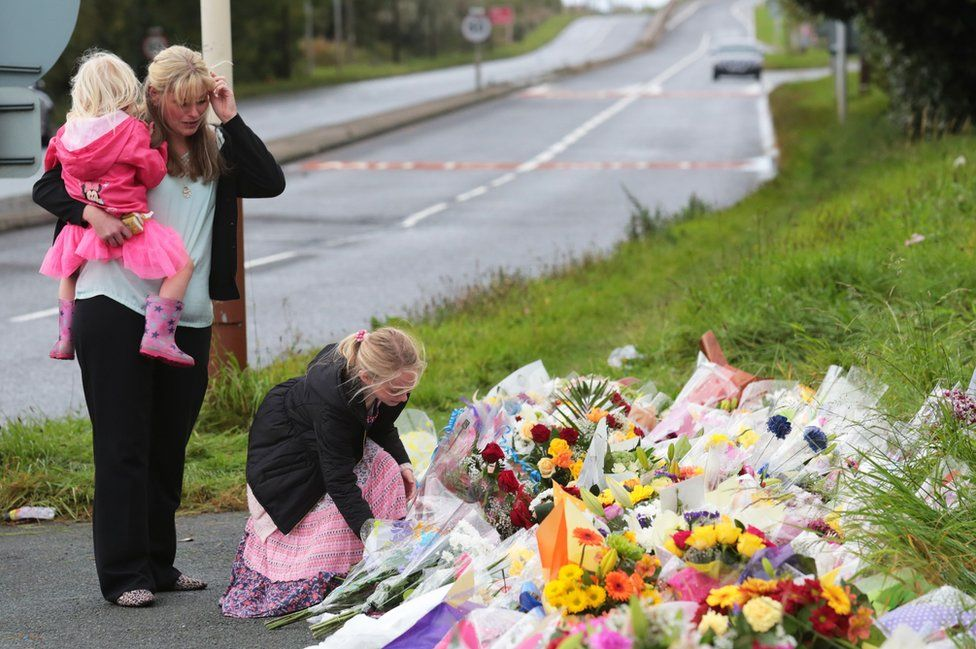 PC Phillip's widow Jen and his daughters leave flowers at the scene of his death