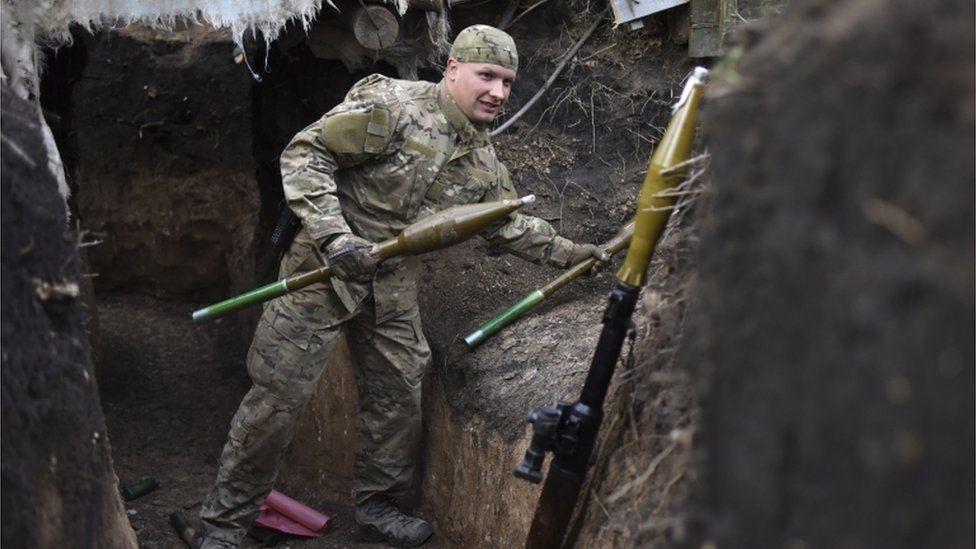 A Ukrainian soldier carrying rocket-propelled grenades in Ukraine's Luhansk region