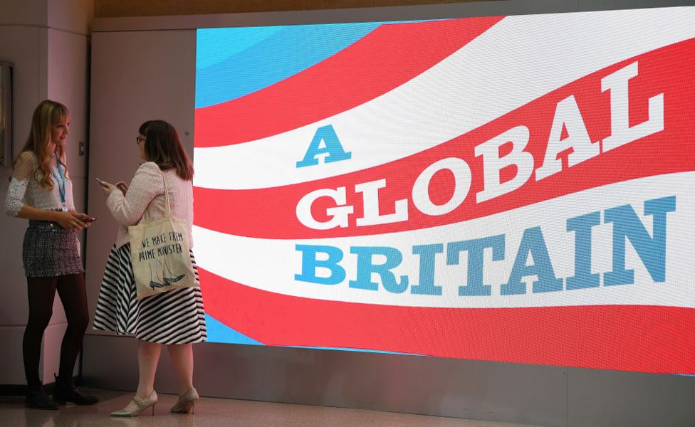 """Young Conservative Party members chat next to a sign that says """"A Global Britain"""" during the annual Conservative Party Conference on September 30, 2018 in Birmingham, England."""