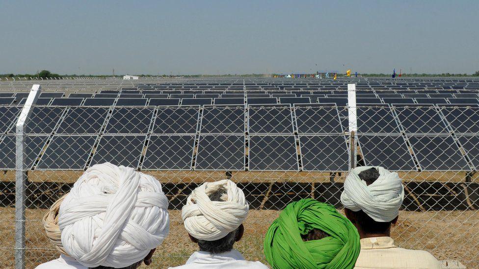 Indian farmers look at a solar farm
