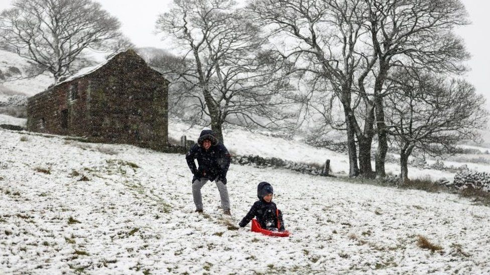 People play in the snow in The Roaches ridge, Staffordshire