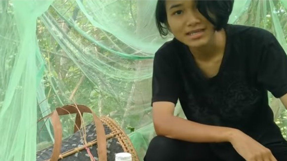 Veveonah sitting in a mosquito net on a platform in a tree