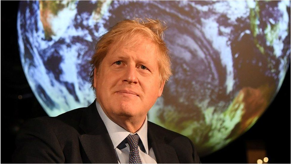 Boris Johnson in front of a globe at a meeting ahead of COP26