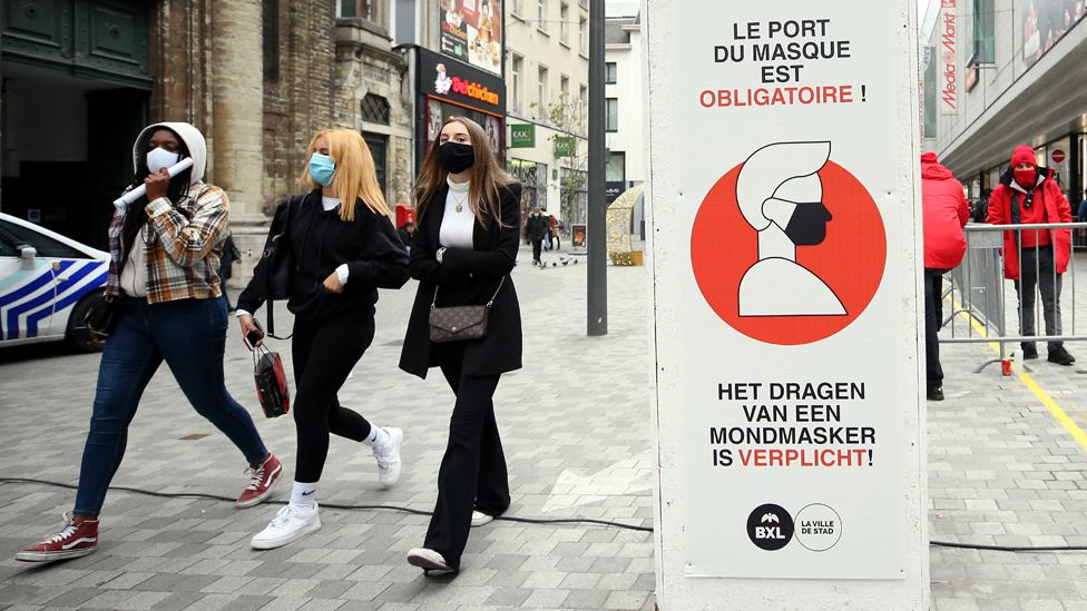 A sign warns people to wear masks in open public areas, in Brussels, Belgium