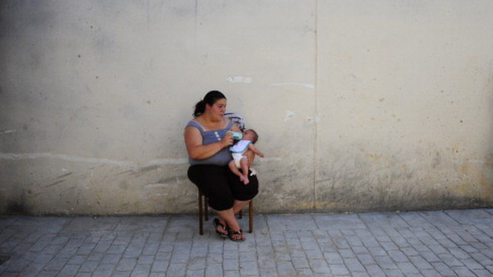 Woman feeds her baby at an abandoned building project on the outskirts of Bollullos Del Condado, Spain (13 June 2013)
