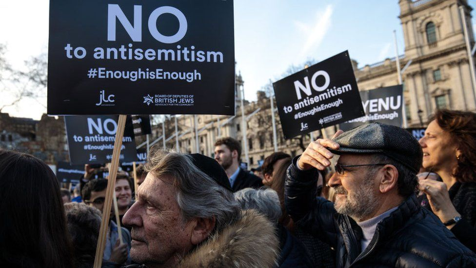 """Protesters holding signs reading """"no to antisemitism #enoughisenough"""""""