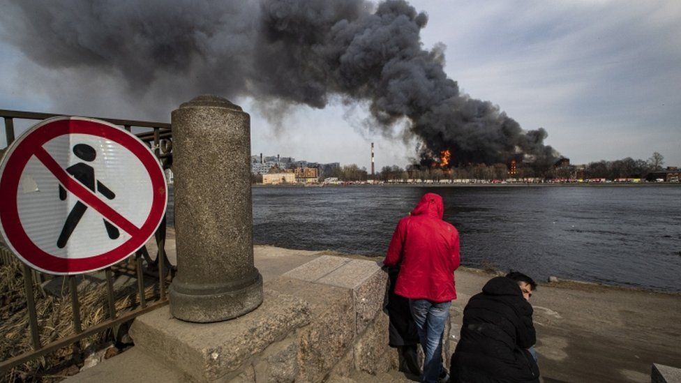 Two people watching smoke from across a river