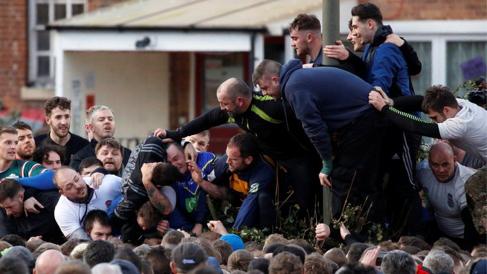 Players fight for the ball during the annual Shrovetide football match in Ashbourne