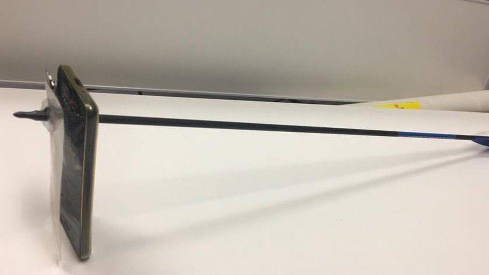 The man's damaged phone seen with an arrow through it
