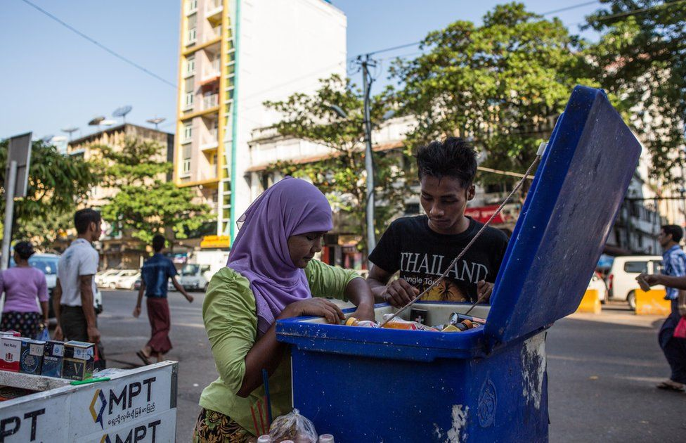 Thwarhairah assists a young man in looking for the right beverage in a cooler that she uses to supplement income from betel nut sales in downtown Yangon, Myanmar, November 14, 2015.