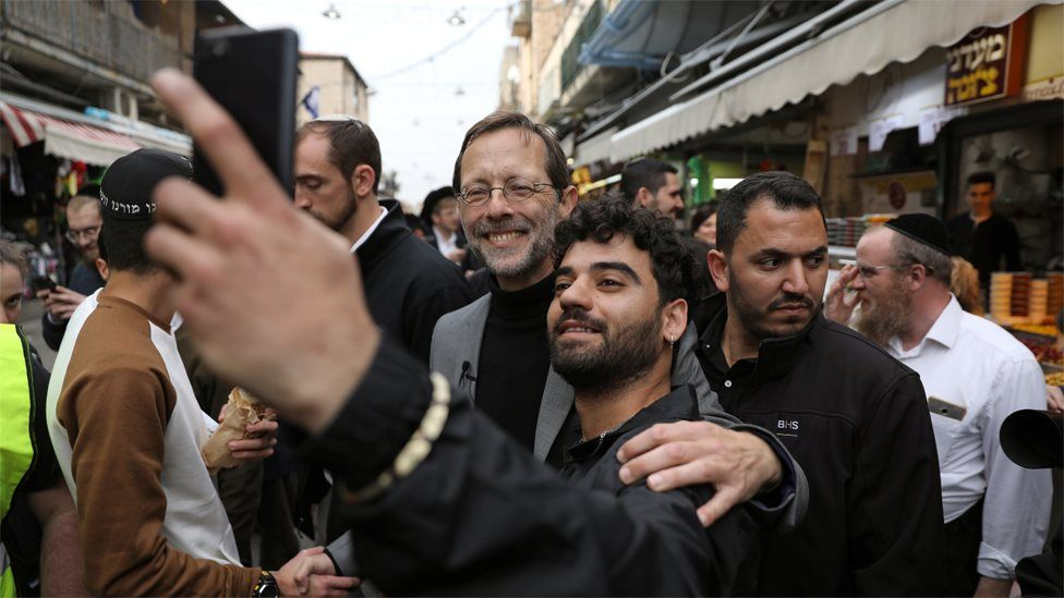 Zehut party leader Moshe Feiglin (C) poses for a selfie with a man at a market in Jerusalem on 4 April 2019