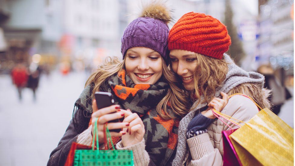 Two women looking at a phone while Christmas shopping