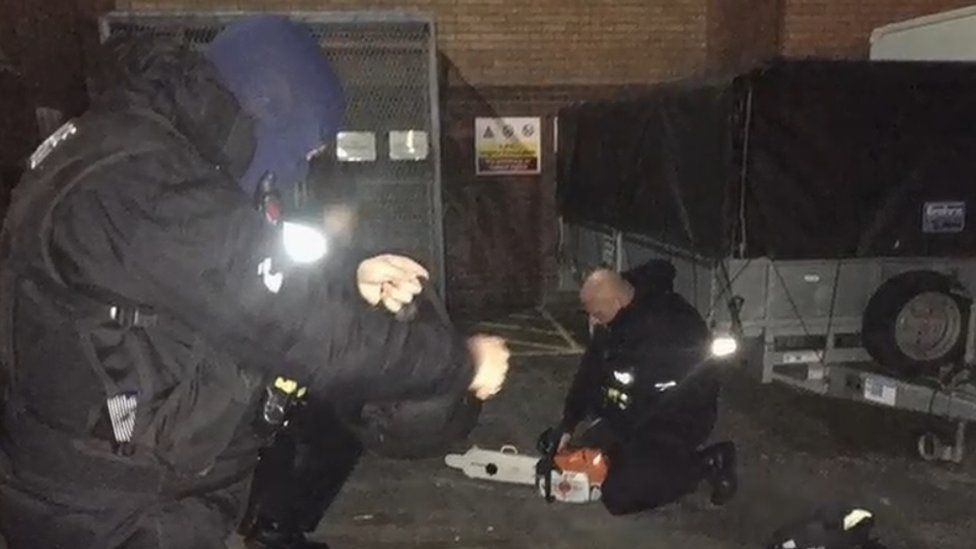 Officers with chainsaw