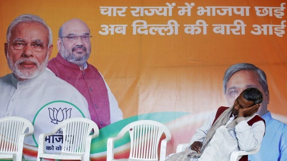 """A worker of Bharatiya Janata Party (BJP) takes a nap in front of the party""""s campaign billboard featuring Prime Minister Narendra Modi (L) and the BJP""""s president Amit Shah at a party office in New Delhi in this February 10, 2015 file photo."""