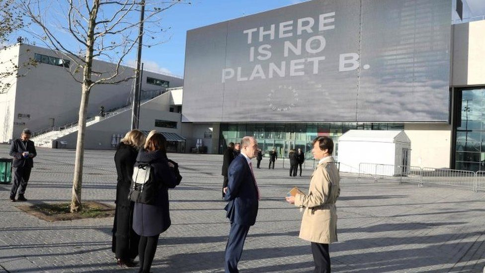 People stand outside La Seine Musicale venue in Boulogne-Billancourt, west of Paris during the One Planet Summit. Photo: 12 December 2017
