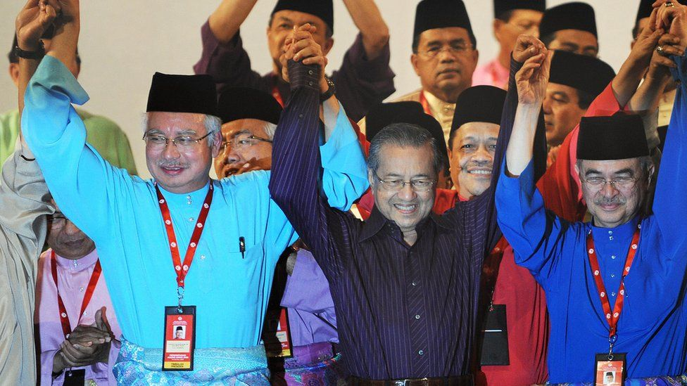 Mahathir (C) and Najib (L) stand at an UMNO annual general assembly meeting in 2009