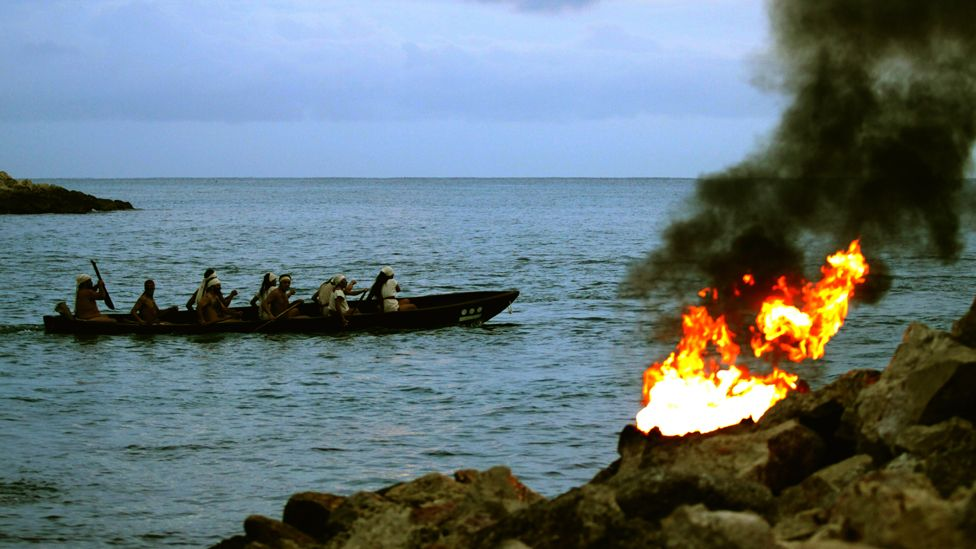 Mayan Indians row in a boat past a fire on the shore as they participate in the ancient ceremony of the 'Mayan Journey' at the ceremonial center of Xcaret