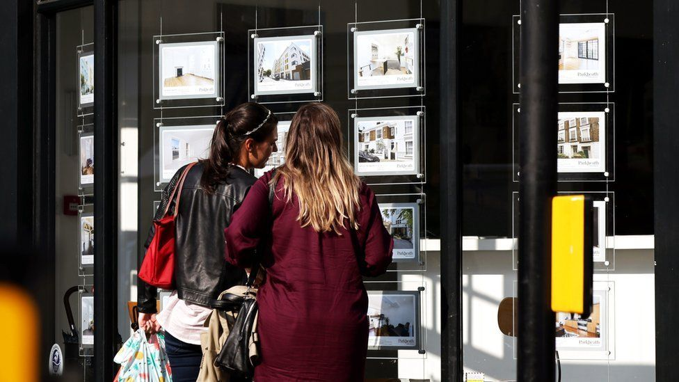 Two women look at homes in an estate agency window