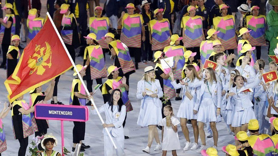 Helpers at the Olympic opening ceremony guide the Montenegro team using brightly coloured ponchos