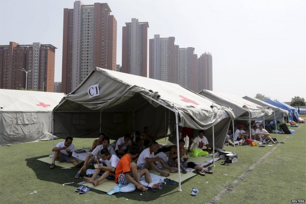 Locals rest under tents at a primary school, which has been turned into a shelter for people living nearby, near the site of the explosions at the Binhai new district, Tianjin, 13 August 2015