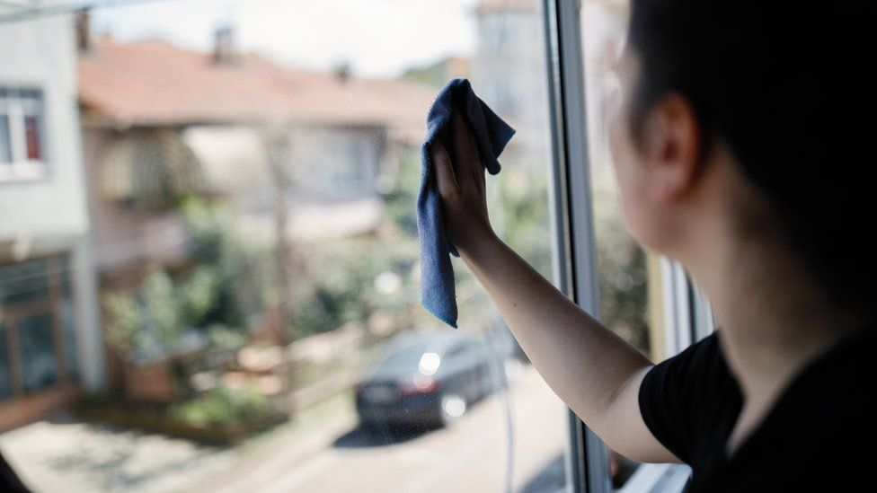 Young woman cleaning window
