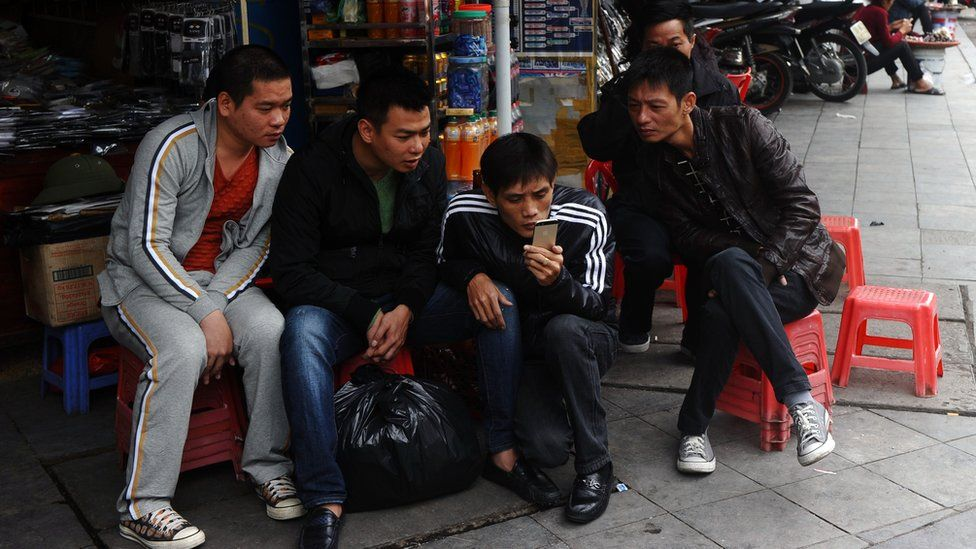 Four men sitting on stools in Vietnam gathered around a single smartphone.