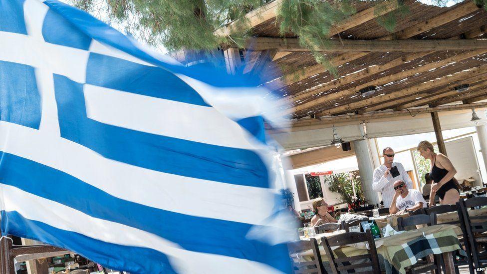 People sit near a Greek flag at a restaurant near Athen