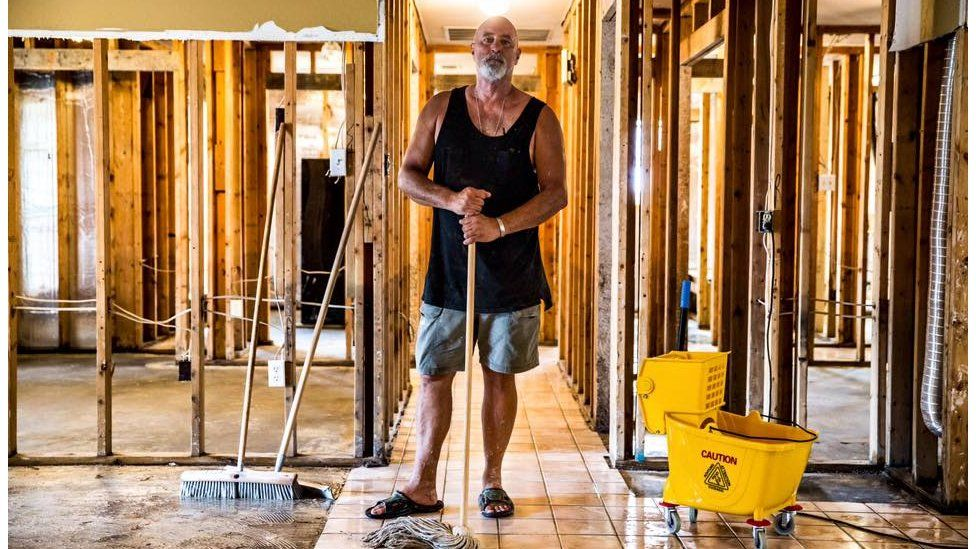 """Phillip """"Mooney"""" Brignac, 58, finishes the clean-up of his home in St Amant. He has lived there since 1991, adding to it while raising two children. """"We will definitely rebuild. We are St Amant strong. We will do whatever we've got to do,"""" he said. St Amant, LA"""