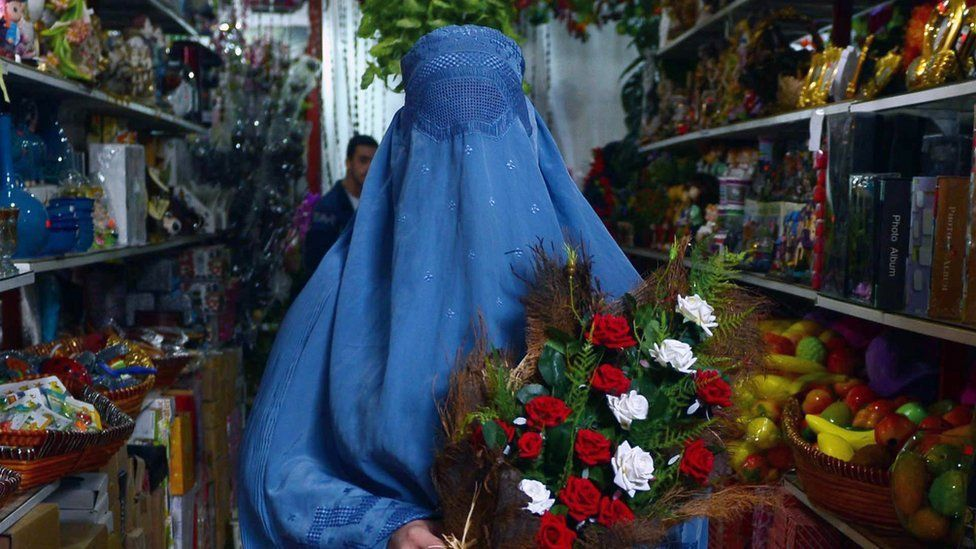 Woman in burqa holding roses