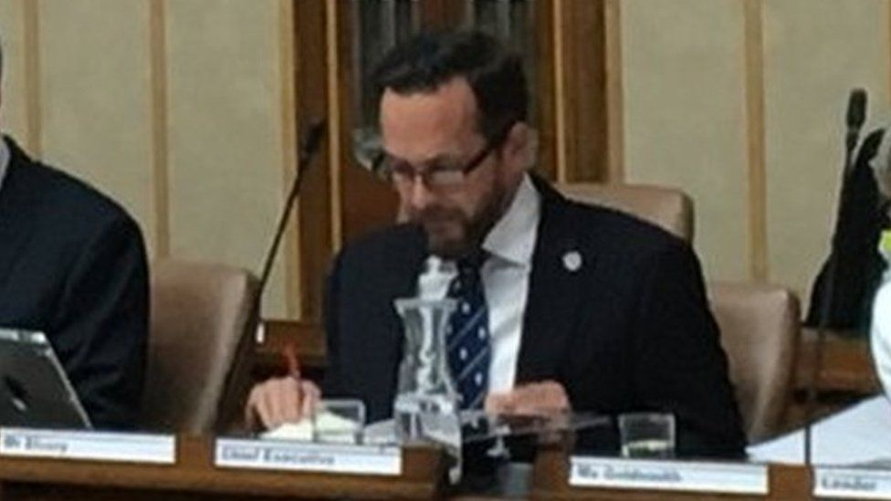 Nathan Elvery sits next to council leader Louise Goldsmith at a full council meeting in July 2019