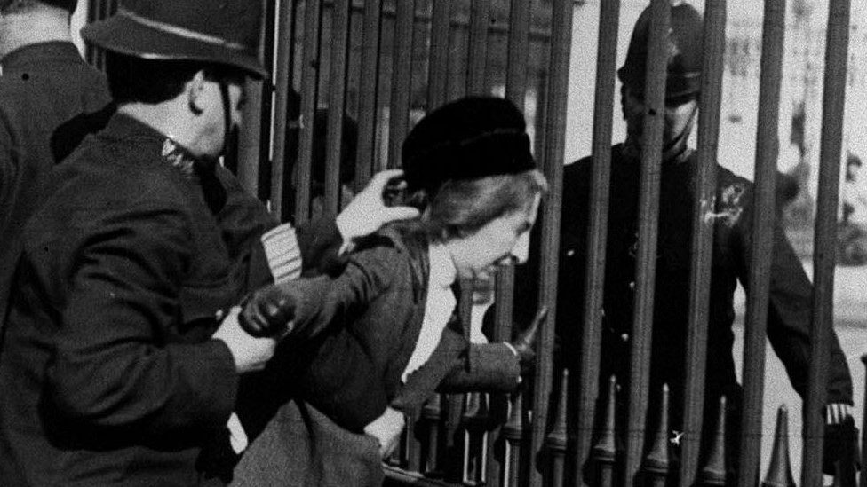 A Suffragette being arrested by police officers during a protest outside Buckingham Palace in 1914