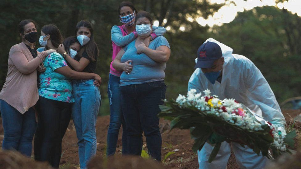 Relatives of a coronavirus victim mourn as their loved one is buried at the Vila Formosa cemetery in Sao Paulo, Brazil, on March 31, 2021