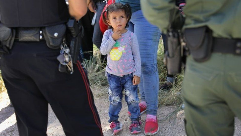 A Mission Police Dept. officer (L) and a US Border Patrol agent watch over a group of Central American asylum seekers before taking them into custody in Texas.