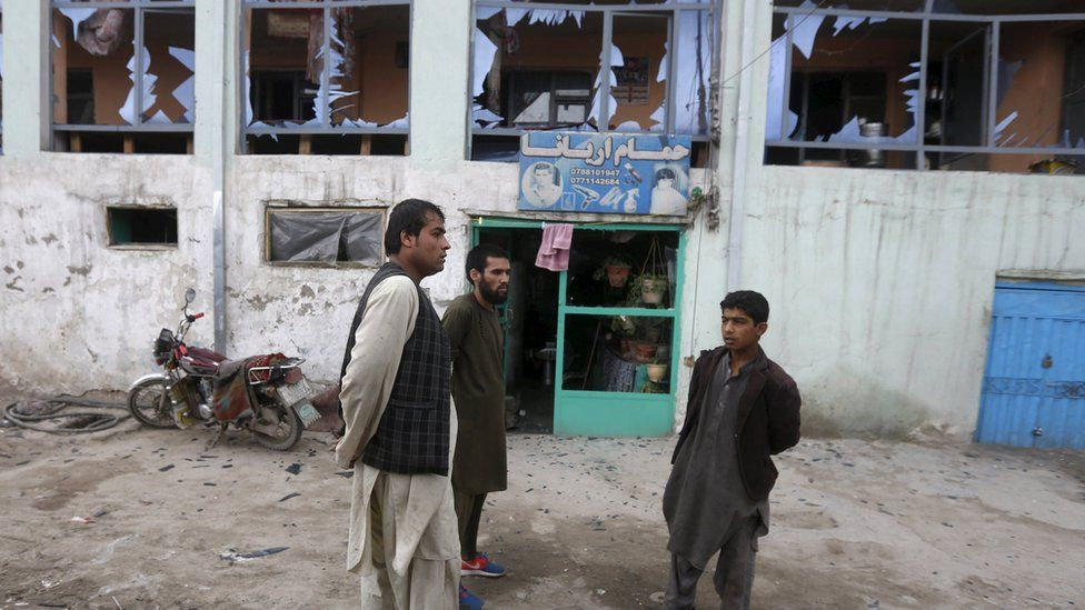 Shopkeepers inspect broken windows after a suicide attack in the Afghan capital Kabul