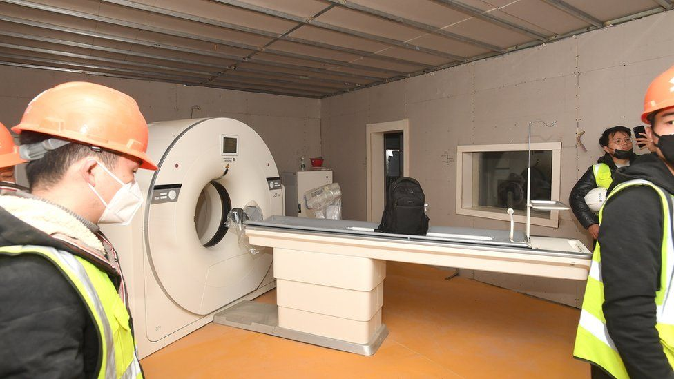 Workers set up a CT scanner inside the hospital