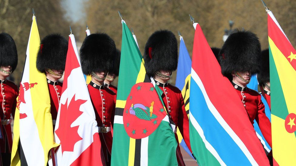 Soldiers of the Coldstream Guards carry flags of the 53 Commonwealth countries