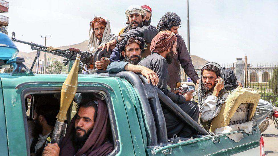 2021 年 8 月 16 日,在阿富汗喀布尔的一辆汽车后面看到塔利班战士
